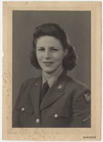 Portrait of Pvt. Dorthy E. Wain Thompson taken while she was stationed in England in 1943. Thompson wears the WAC winter service uniform with the 8th Air Force patch on her shoulder.