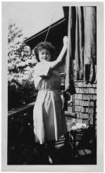"""Ann Kaplowitz Goldberg poses in her brown and white seersucker exercise uniform while hanging laundry on the back porch of her quarters in Asheville, North Carolina, nicknamed """"khalamity kottage"""" on 10 July 1945. The back of the photo reads, """"Glamorous, even when I'm washing clothes. The window is my bedroom."""" The University of North Carolina at Greensboro, University Libraries, PO Box 26170, Greensboro NC 27402-6170, 336.334.5304 -- http://library.uncg.edu/"""