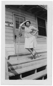 """Ann Kaplowitz Goldberg leans against a mop on the porch of Barracks 12 at Fort Oglethorpe, Georgia, in March 1945, wearing her work uniform and Daisy Mae fatigue cap. The back of the photo reads, """"Don't I look like an eager beaver?"""" The University of North Carolina at Greensboro, University Libraries, PO Box 26170, Greensboro NC 27402-6170, 336.334.5304 -- http://library.uncg.edu/"""