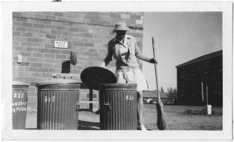 Doris Dickens Wilson holds a broom while lifting the lid of a garbage can, part of her Kitchen Patrol duties. Photo identification indicates she was wearing her fatigue uniform. The University of North Carolina at Greensboro, University Libraries, PO Box 26170, Greensboro NC 27402-6170, 336.334.5304 -- http://library.uncg.edu/
