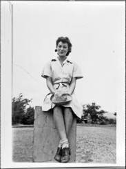 Kathryn Fulner Wakefield sits on a post, circa 1943. She wears the WAAC brown and white seersucker exercise uniform, and in her lap is the khaki summer fatigue hat. The University of North Carolina at Greensboro, University Libraries, PO Box 26170, Greensboro NC 27402-6170, 336.334.5304 -- http://library.uncg.edu/