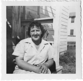 Marcelle Fisher poses outside a barracks in the WAC seersucker exercise uniform, circa 1943. Behind her, laundry is hanging to dry. The University of North Carolina at Greensboro, University Libraries, PO Box 26170, Greensboro NC 27402-6170, 336.334.5304 -- http://library.uncg.edu/
