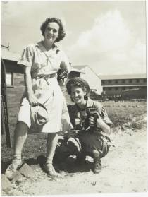 Two WACs pose at MacDill Airfield in Tampa, Florida, circa 1943. The WAC on the left wears the brown and white seersucker exercise uniform and holds her Daisy Mae cap. The WAC crouching on the right wears a men's flight suit with air force insignia and a Daisy Mae cap, and holds a camera. The University of North Carolina at Greensboro, University Libraries, PO Box 26170, Greensboro NC 27402-6170, 336.334.5304 -- http://library.uncg.edu/