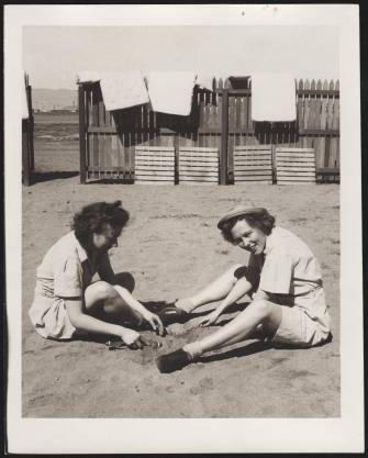 WACs Bernice Moran Miller and Elsie Ribiero play in the sand at Peterson Field, Colorado Springs, in 1943. Behind them, mattresses are draped over a wooden fence. The University of North Carolina at Greensboro, University Libraries, PO Box 26170, Greensboro NC 27402-6170, 336.334.5304 -- http://library.uncg.edu/