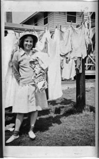 """Helena Seymbroski("""" stands in front of a clothesline holding a box of Rinso detergent on wash day at Fort Oglethorpe, Georgia, April 1944. The University of North Carolina at Greensboro, University Libraries, PO Box 26170, Greensboro NC 27402-6170, 336.334.5304 -- http://library.uncg.edu/"""